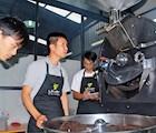Anh Trần Nhật Quang (giữa) đang kiểm tra công đoạn rang xay cà phê tại xưởng sản xuất của mình