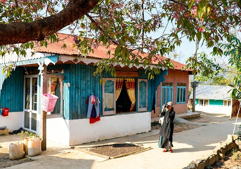 Khách du lịch dạo chơi,ngắm những căn nhà gỗ đầy màu sắc ở thôn Đạ Blah. Ảnh: N.T