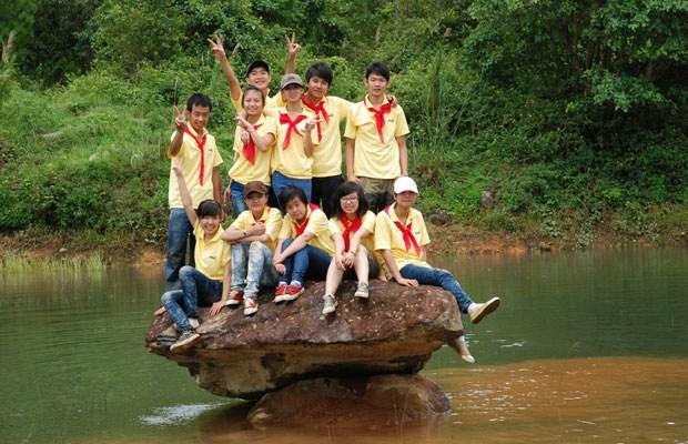 Nhóm học sinh đi tham quan Khu di tích căn cứ núi Voi chụp hình lưu niệm bên hồ núi Voi