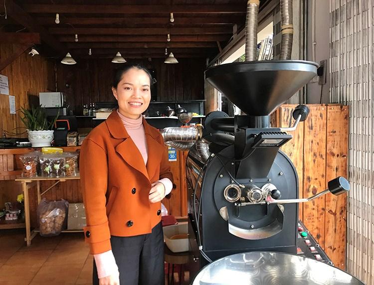 Trần Thị Huyền bên máy rang cà phê